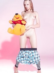 Admirable teen beauty in striped gaiters with a teddy bear undressing and spreading legs.