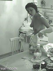 Nude brunette woman having her breakfast