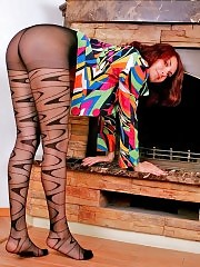 Cute redhead Bella posing in fashion pantyhose near the fireplace