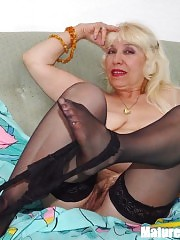 Lustful blonde mature in black stockings undressing and playing with pussy