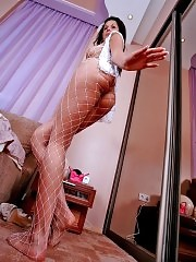 Busty brunette Juliana in white fishnet pantyhose posing near the mirror
