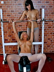 Two gym chicks in tights pumping iron