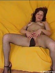 Busty brunette hottie with nice ass posing in fishnet pantyhose