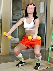 Brunette Gretta in pantyhose working out with dumbbells