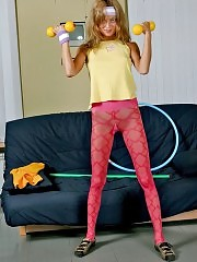 Redheaded Ladyb in red pantyhose working out with dumbbells