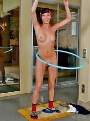 Seductive redhead hula hooping in the pink