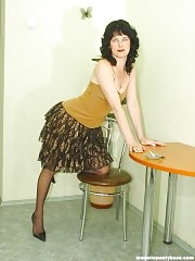 Mature lady is smoking in only pantyhose