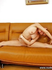 Flexible beauty with long sexy legs posing on the sofa
