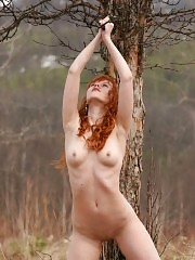 Thrilling captivating angel is walking alone in the deserted autumn field and gaily dances near the lonely old tree.