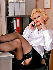 Blonde secretary Lindsey in black stockings playing with her pussy