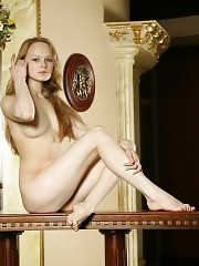 Pretty girl enjoys posing totally naked at and on the table on camera.